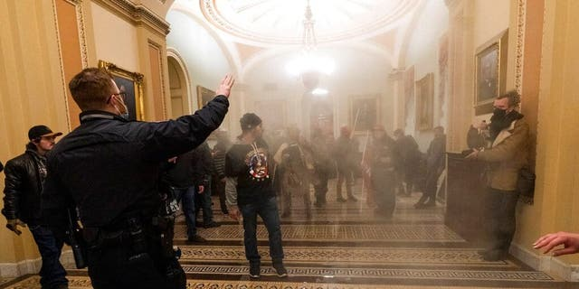 FILE - In this Jan. 6, 2021, file photo, smoke fills the walkway outside the Senate Chamber as violent rioters loyal to President Donald Trump are confronted by U.S. Capitol Police officers inside the Capitol in Washington. New details from the deadly riot of Jan. 6 are contained in a previously undisclosed document prepared by the Pentagon for internal use that was obtained by the Associated Press and vetted by current and former government officials. (AP Photo/Manuel Balce Ceneta, File)